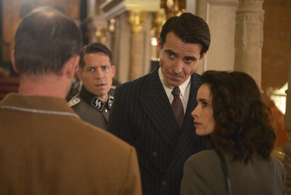 "TIMELESS -- ""Party At Castle Varlar"" Episode 103 -- Pictured: (l-r) Sean Maguire as Ian Fleming, Goran Visnjic as Garcia Flynn, Abigail Spencer as Lucy Preston -- (Photo by: Sergei Bachlakov/NBC)"